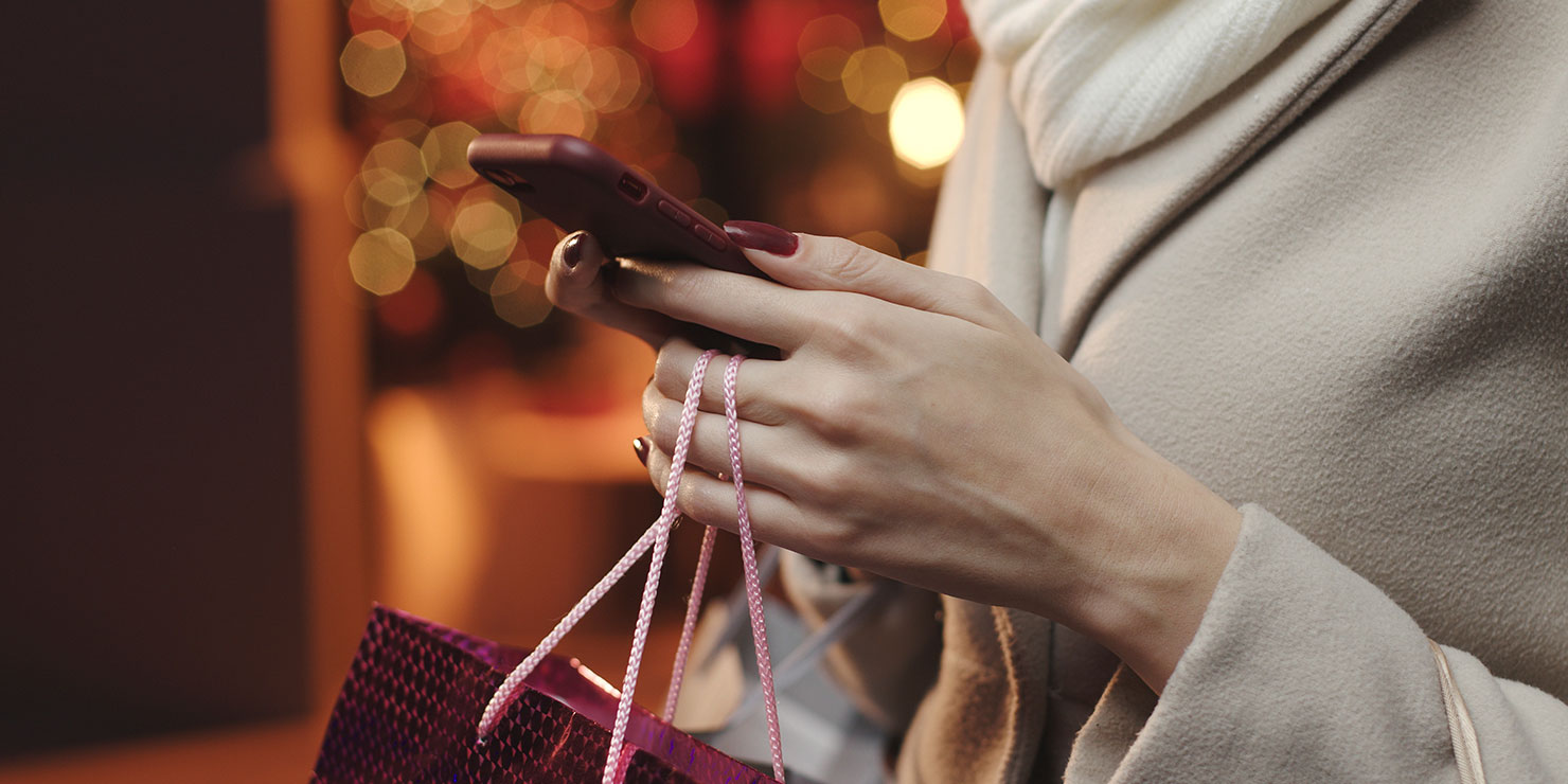 Hands holding iphone and shopping bag